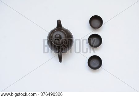 A New Kettle With Three Cups On White Background