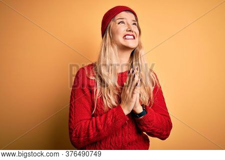 Young beautiful blonde woman wearing casual sweater and wool cap over white background begging and praying with hands together with hope expression on face very emotional and worried. Begging.