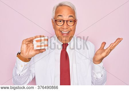 Middle age senior grey-haired dentist man holding prosthesis denture over pink background very happy and excited, winner expression celebrating victory screaming with big smile and raised hands