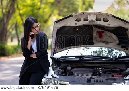 A Young Asian Woman Is Calling Her Service Technician To Fix A Broken Car On The Side Of The Road, D