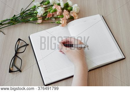Female Hand Writing Notes In Daily Planner. Open Daily Planner, Bouquet Of Carnation Flowers, Glasse