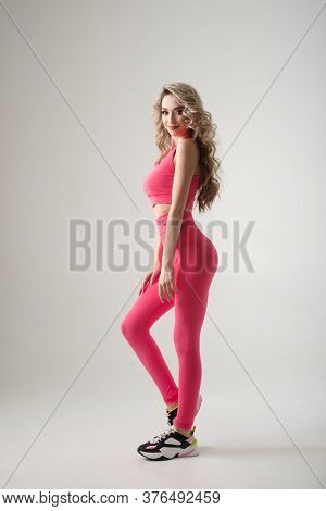 Attractive female in sporty shape wearing pink sportswear isolated on white background in studio. Full lenght portrait