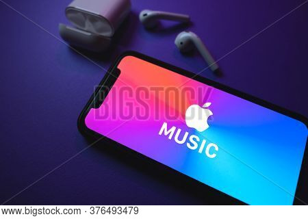 Apple Music Logo On The Smartphone Screen, With Airpods. High Quality Photo