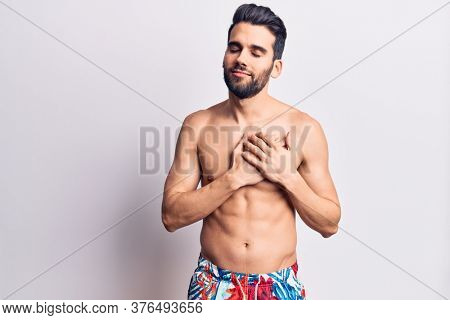 Young handsome man with beard shirtless wearing swimwear smiling with hands on chest, eyes closed with grateful gesture on face. health concept.