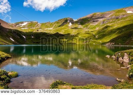 Mountain Ridge With Small Spots Of Snow Reflecting In A Small Mountain Lake Near The Bachalpsee, Hig