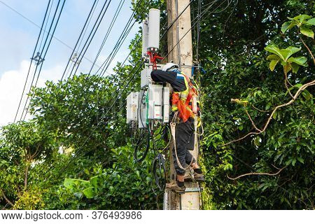 A Professional Electrician Performs Installation Work On A Pole. An Electrician In Professional Equi