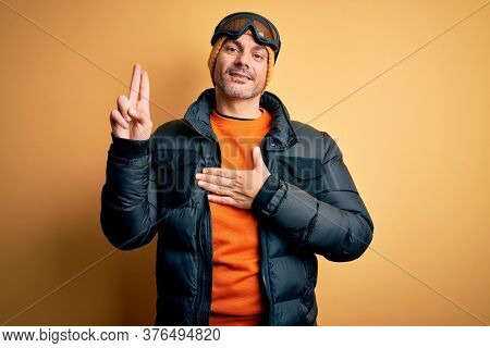 Young handsome skier man skiing wearing snow sportswear using ski goggles smiling swearing with hand on chest and fingers up, making a loyalty promise oath