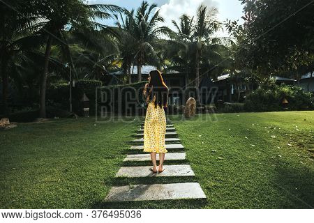 Young Woman Walks In A Yellow Dress On A Tropical Grove With Green Grass On A Sunny Day. Background