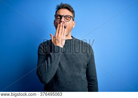 Young handsome man wearing casual sweater and glasses standing over blue background bored yawning tired covering mouth with hand. Restless and sleepiness.