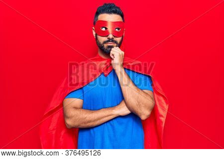 Young hispanic man wearing super hero costume thinking concentrated about doubt with finger on chin and looking up wondering