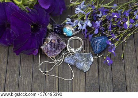 Semiprecious Stones - Amethyst, Agate, Sodalite Lie On A Wooden Background. Nearby Are Silver Rings