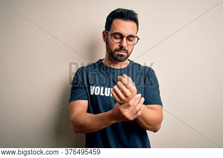 Handsome man with beard wearing t-shirt with volunteer message over white background Suffering pain on hands and fingers, arthritis inflammation