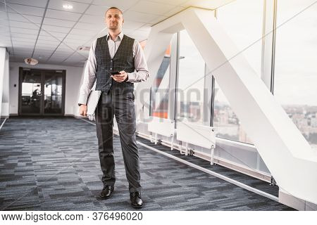 A Tall Handsome Stately Man Entrepreneur In A Formal Suit With A Vest Is Standing In A Long Corridor
