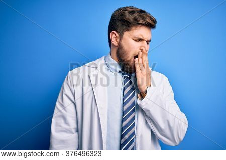 Young blond therapist man with beard and blue eyes wearing coat and tie over background bored yawning tired covering mouth with hand. Restless and sleepiness.