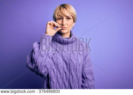 Young blonde woman with short hair wearing winter turtleneck sweater over purple background mouth and lips shut as zip with fingers. Secret and silent, taboo talking