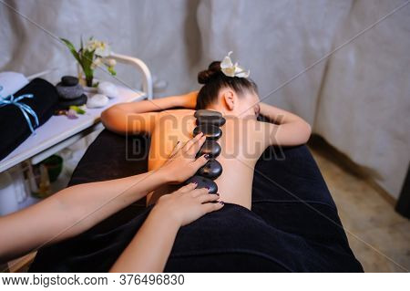 Stone Therapy On A Female Client In Beauty Spa Lateral View