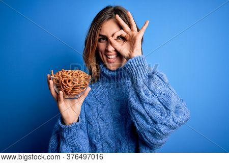 Young beautiful brunette woman holding bowl german baked pretzels over blue background with happy face smiling doing ok sign with hand on eye looking through fingers