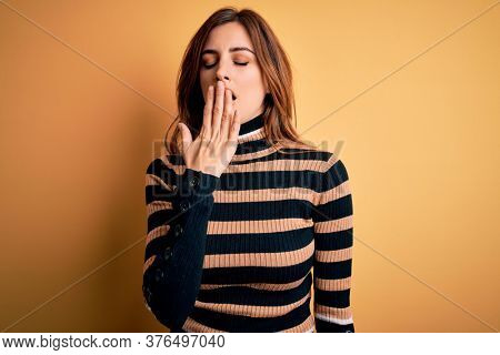 Young beautiful brunette woman wearing striped turtleneck sweater over yellow background bored yawning tired covering mouth with hand. Restless and sleepiness.