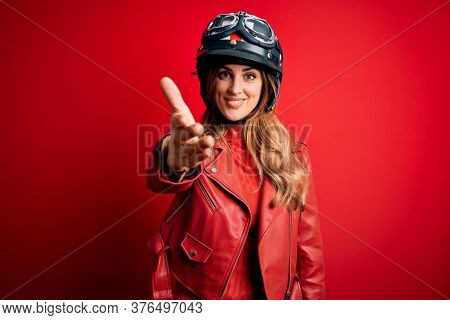 Young beautiful brunette motrocyclist woman wearing moto helmet over red background smiling friendly offering handshake as greeting and welcoming. Successful business.