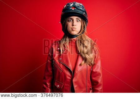 Young beautiful brunette motrocyclist woman wearing moto helmet over red background puffing cheeks with funny face. Mouth inflated with air, crazy expression.