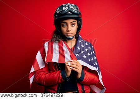 African american patriotic motorcyclist girl wearing moto helmet wearing united states flag with a confident expression on smart face thinking serious