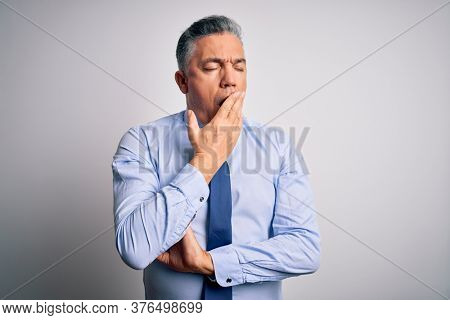 Middle age handsome grey-haired business man wearing elegant shirt and tie bored yawning tired covering mouth with hand. Restless and sleepiness.