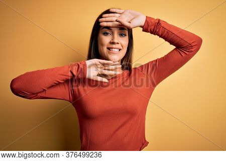 Young beautiful brunette woman wearing casual t-shirt standing over yellow background Smiling cheerful playing peek a boo with hands showing face. Surprised and exited