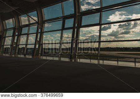 Copenhagen, Denmark - April 30, 2020: Airport Windows With Cloudy Sky And Airfield At Background In