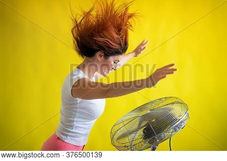 A Beautiful Red-haired Woman Is Cooled Off Standing Over A Large Electric Fan On A Yellow Background