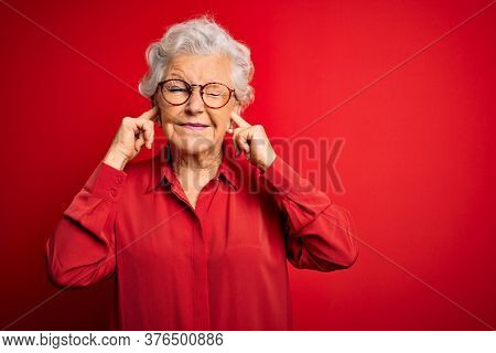 Senior beautiful grey-haired woman wearing casual shirt and glasses over red background covering ears with fingers with annoyed expression for the noise of loud music. Deaf concept.
