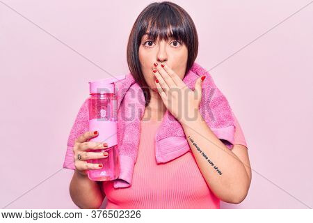 Young plus size woman wearing sportswear and towel holding water bottle covering mouth with hand, shocked and afraid for mistake. surprised expression
