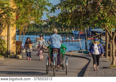 Cyclo Rider Cycling Through A Riverside Street In The Late Afternoon Sun, Hoi An, Vietnam - January