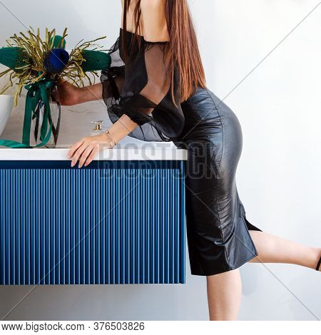Woman In A Tight Leather Skirt Bending To Grab A Vase From A Table. Cropped