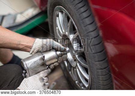 Repair Or Changing Tire Car Vehicle Mechanic Screwing Car Wheel At Repair Service Station