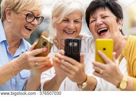 Group of senior women using smartphones together