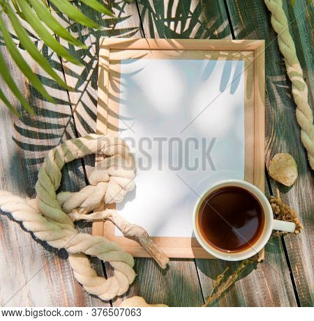 Mock up with empty wooden frame, rope and cup of coffee, outdoor summer photo, marine style, palm shadows