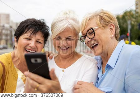 Group of senior women using mobile phone together