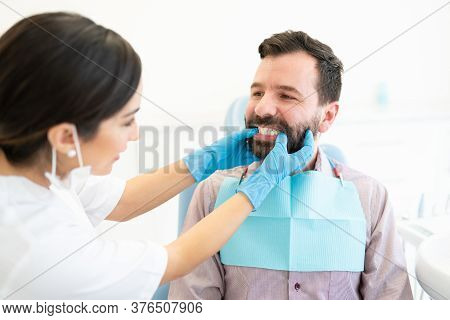 Female Dentist Checking Teeth Of Mid Adult Man At Orthodontic Clinic