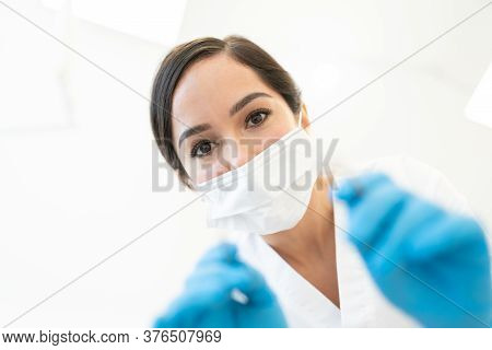 Caucasian Mid Adult Female Dentist Wearing Face Mask, See From Below
