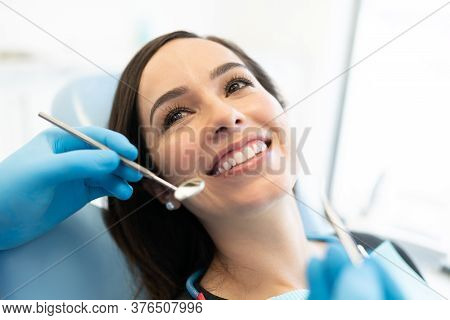 Dentist Checking Caucasian Woman With Carver And Mirror At Dental Clinic
