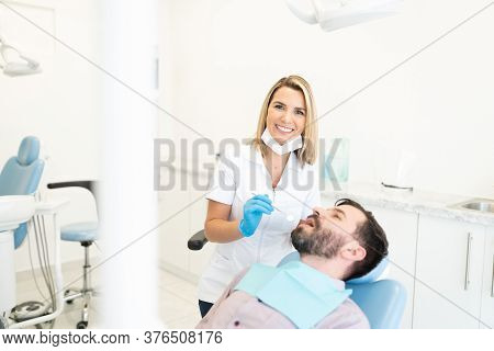 Confident Mid Adult Female Dentist Checking A Patient's Teeth In A Dental Clinic
