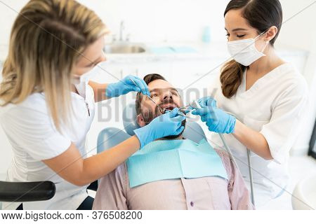 Couple Of Dentists Examining Mid Adult Man During Dental Treatment At Clinic