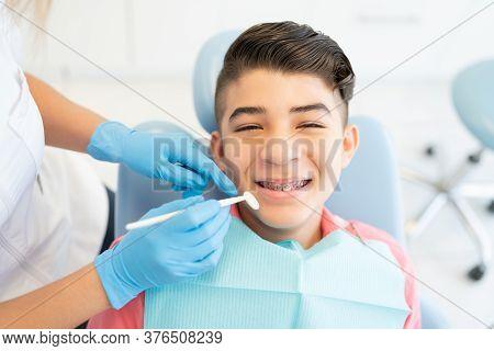 Dentists Examining Smiling Teenage Boy With Dental Mirror At Clinic