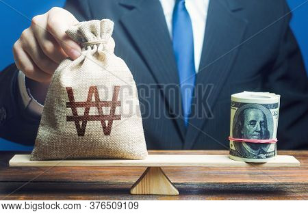 A Man Puts South Korean Won Money Bag On The Scales Opposite To The Dollar. Protecting Savings From