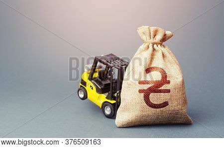 A Yellow Forklift Cannot Lift A Ukrainian Hryvnia Money Bag. Interest Rate. Stimulating Economy. Hel