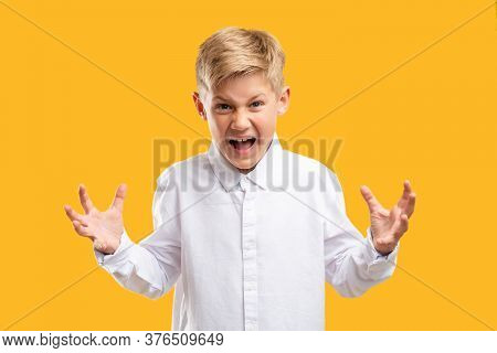 Angry Child Portrait. Child Anxiety. Annoyed Boy In White Shirt Yelling Raising Hands Isolated On Or