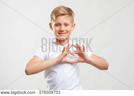 Love Sign. Affection Compassion. Friendly Blond Boy Showing Heart Gesture Isolated On Neutral Backgr