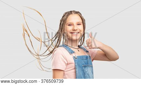 Satisfied Kid Portrait. Like Gesture. Playful Teen Girl Showing Thumb Up Smiling Isolated On White B