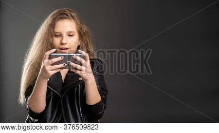 Mobile Game Addiction. Online Entertainment. Excited Teen Girl Playing On Phone Isolated Dark Copy S