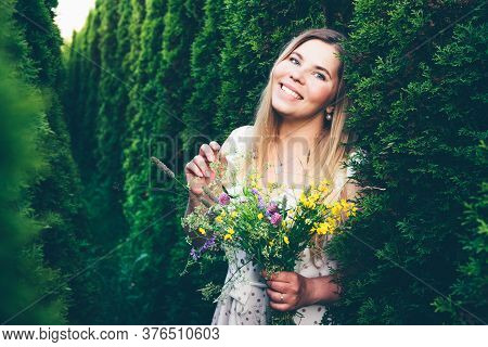Smiling Young Overweight Girl With A Bouquet Of Wildflowers On A Background Of Conifers In A White D